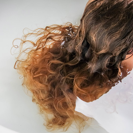 woman's curly hair in a bath tub of water