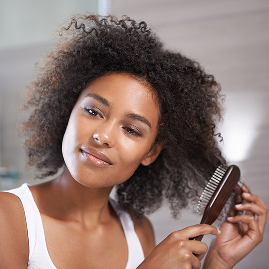woman brushing her curly hair