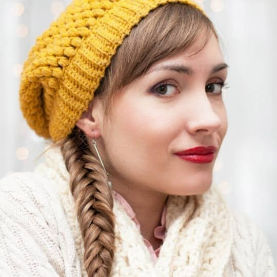 Woman with fishtail braids wearing a beanie hat