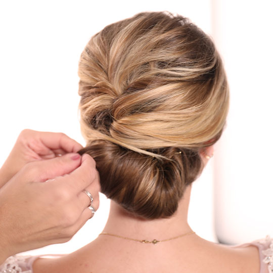 hand pinning bun in woman's updo