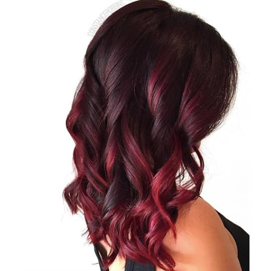 A woman with a beautiful magenta hairstyle