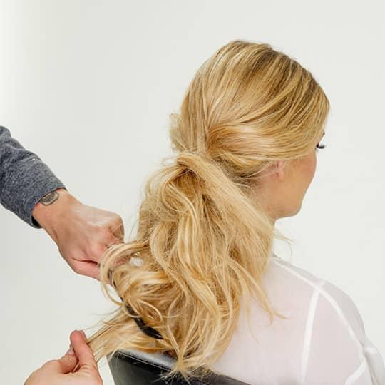 man teasing woman's hair for new years eve bun