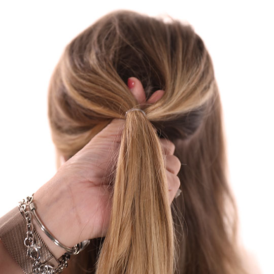 thumbs through a loop in a half ponytail