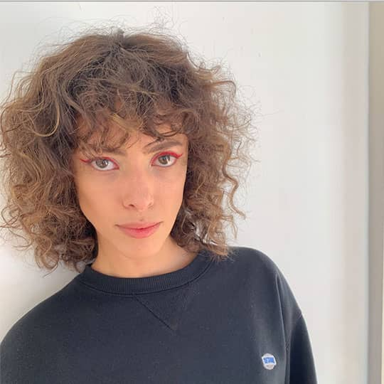 woman with curly hair at paris fashion week