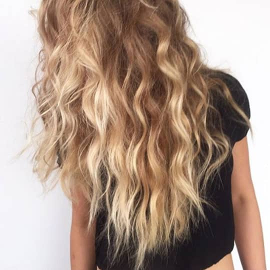 woman with blond long wavy hairstyle