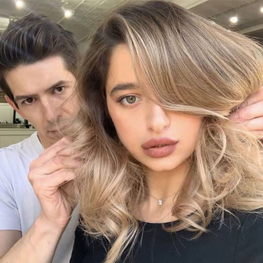 man holding hair of woman with airtouch technique balayage