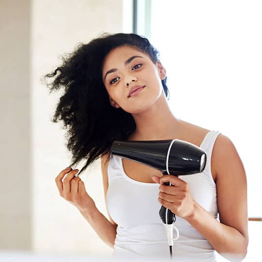 woman blow drying her natural texture hair