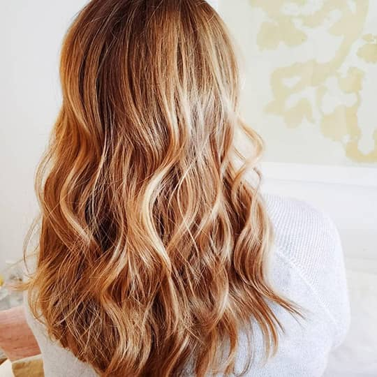 photo of woman with light copper hair and honey highlights