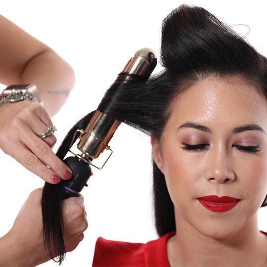 hair wrapped around curling iron for old hollywood waves style