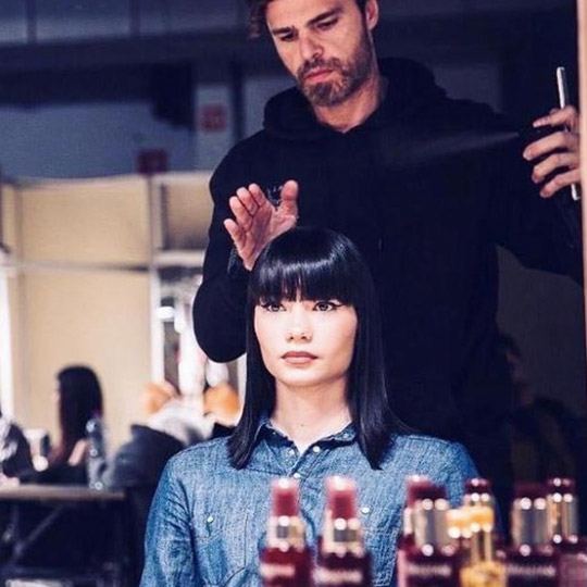 woman with black hair and bangs getting her hair styled