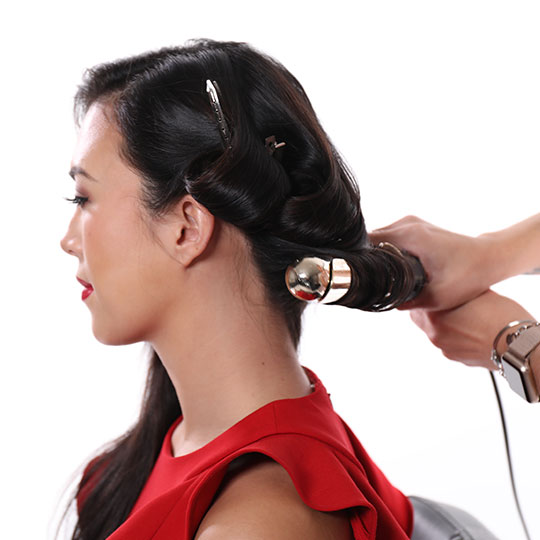 hand holding curling iron for old hollywood waves style