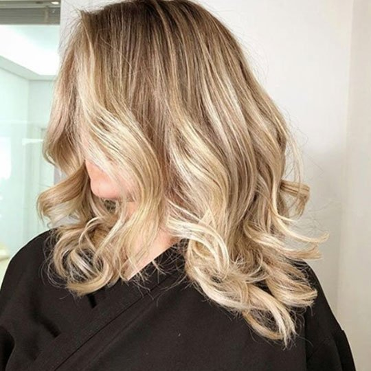 woman with blonde hair in salon cape
