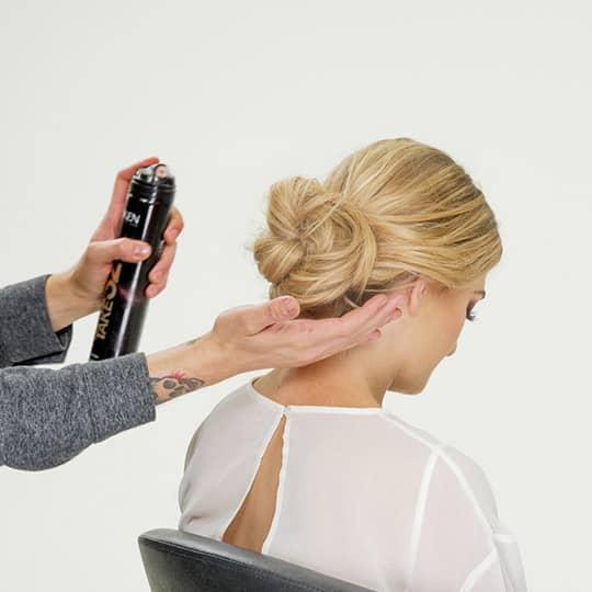 man spraying woman's new years eve hair