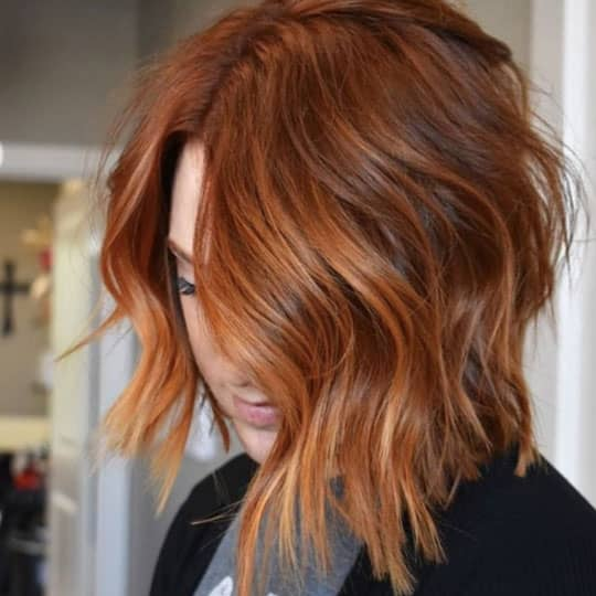woman with balayage red hair in a lob